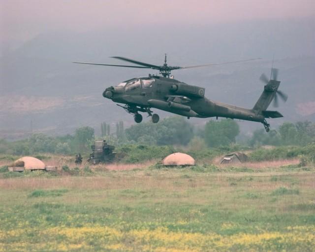 23 Απριλίου 1999 Α/Δ Rinas. Ε/Π Apache σε πτήση εξοικειώσεως. Στο βάθος φαίνονται τα χαρακτηριστικά πολυβολεία της εποχής του Εμβέρ Χότζα (U.S. Air Force photo by Tech. Sgt. Cesar Rodriguez) (RELEASED)