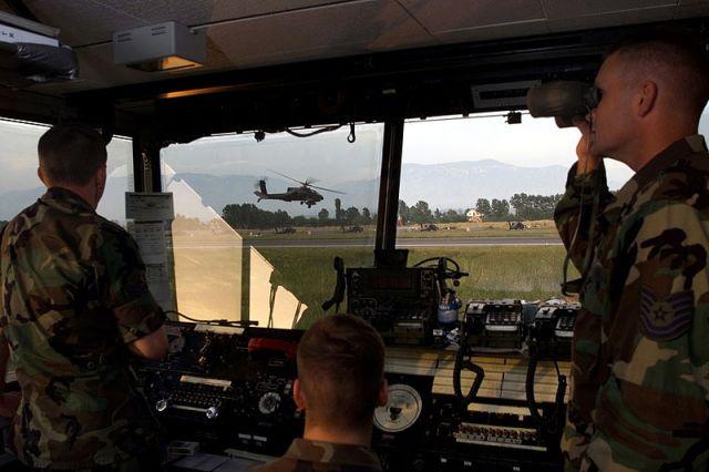 Ο Technical Sgt(TSgt) Joe Odom(δεξιά),Ελεγκτής Εναέριας Κυκλοφορίας του 46th Operation Support Squadron, από την αεροπορική βάση Eglin της Florida, ελέγχει και συντονίζει την κίνηση των αεροπορικών μέσων στο Α/Δ Rinas στις 31 Μαΐου 1999. Ο έλεγχος του Α/Δ γινόταν από μικτό προσωπικό της ΠΑ και της ΑΣ των ΗΠΑ.
